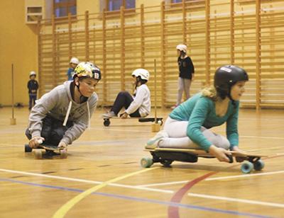 młodzież ucząca się jazdy na lonboardzie elektrycznym